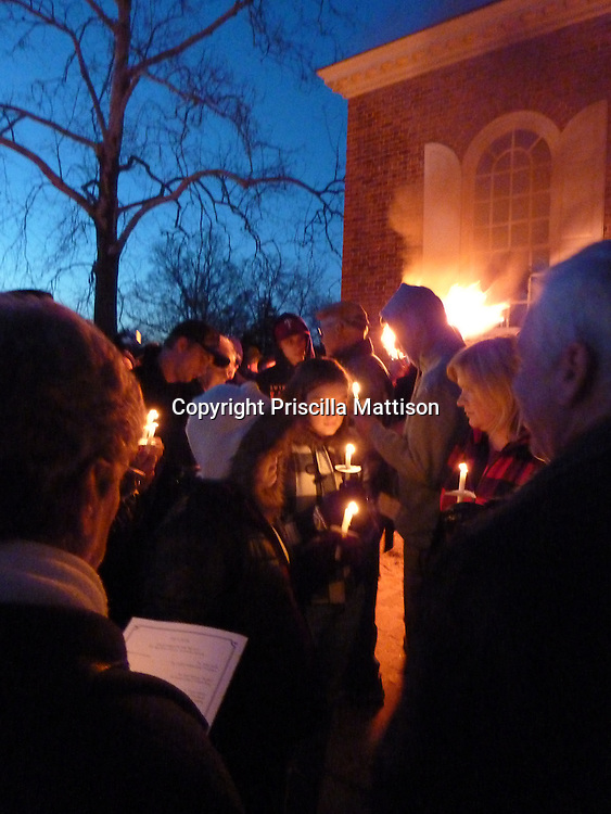Williamsburg, Virginia - December 24, 2010:   Glowing candles and a smoking torch light the scene in front of the courthouse during the Williamsburg Community Christmas Tree Ceremony.
