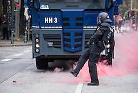 """Proteste gegen Naziaufmarsch """"Tag der Patrioten"""".<br /> Mehere zehntausend Menschen protestirten am Samstag den 12. September 2015 in Hamburg gegen einen von Nazis und Hooligans geplanten Aufmarsch unter dem Motto """"Tag der Patrioten"""". Der Aufmarsch war im Vorfeld gerichtlich untersagt worden, da davon auszugehen sei, dass von ihm Gewalttaten gegen Personen ausgehen wuerden. Die Nazis wichen am Samstag daraufhin nach Bremen aus, wo der Aufmarsch jedoch auch untersagt wurde.<br /> Trotz Verbot versammelten sich an verschiedenen Orten in Hamburg mehrere zehntausend Menschen und protestierten gegen Rassismus und fuer ein Bleiberecht fuer gefluechtete Menschen.<br /> Vor dem Hauptbahnhof kam es zu kleineren Auseinandersetzungen mit der Polizei, die mit 8 Wasserwerfern, Polizeihubschrauber und Beamten aus Bayern, Schleswig-Holstein, Baden-Wuertemberg und Hamburg im Einsatz war.<br /> Als eine Gruppe von ca. 10 bis 15 Nazis und Hooligans im Hauptbahnhof Menschen angriffen, drohte die Lage kurzzeitig zu eskalieren. Die Angreifer mussten aber vor Gegendemonstranten in einen Zug fluechten, wo sie von der Polizei festgesetzt wurden. Der Verkehr durch den Hauptbahnhof war ueber lange Zeit eingestellt, da die Polizei weitere Nazis und Hooligans in ankommenden Zuegen befuerchtete und Auseinandersetzungen verhindern wollte.<br /> Im Bild: Ein Rauchkoerper wurde in Richtung Polizeigeworfen und ein Beamter tritt ihn weg.<br /> 12.9.2015, Hamburg<br /> Copyright: Christian-Ditsch.de<br /> [Inhaltsveraendernde Manipulation des Fotos nur nach ausdruecklicher Genehmigung des Fotografen. Vereinbarungen ueber Abtretung von Persoenlichkeitsrechten/Model Release der abgebildeten Person/Personen liegen nicht vor. NO MODEL RELEASE! Nur fuer Redaktionelle Zwecke. Don't publish without copyright Christian-Ditsch.de, Veroeffentlichung nur mit Fotografennennung, sowie gegen Honorar, MwSt. und Beleg. Konto: I N G - D i B a, IBAN DE58500105175400192269, BIC INGDDEFFXXX, Kontakt: post@christian-dits"""