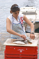 A young woman selling fish on the street market, de-scaling the fish. Collioure. Roussillon. France. Europe.