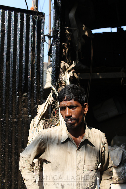 A man stands in the doorway of a market in central Kolkata, India. November, 2013