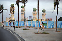 Senegal. Dakar. Early morning, men walk on a sidewalk near a mosque with four minarets painted in green color. Palm trees. 04.12.09  © 2009 Didier Ruef