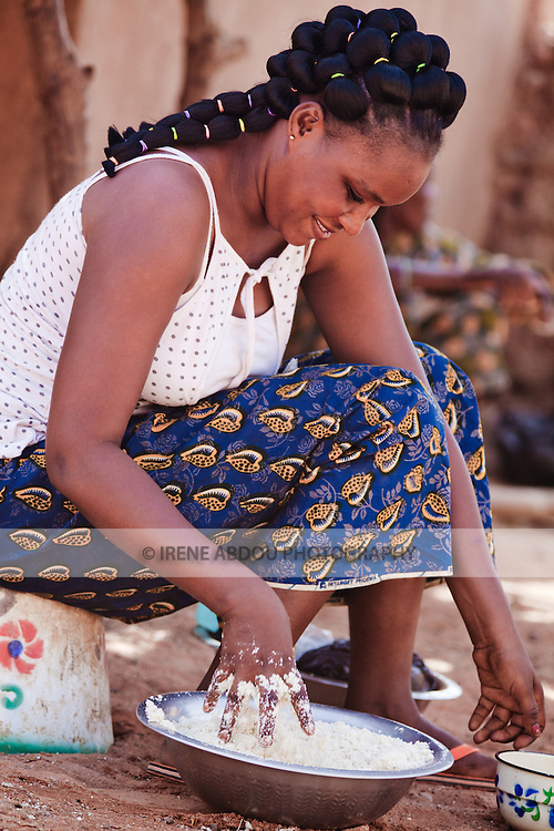 A Fulani woman in the town of Djibo in northern Burkina Faso kneads manioc powder, which she will use to make couscous.