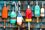 colorful fishing buoys hanging on weathered wood building