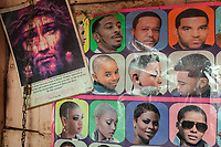 Nigeria. Enugu State. Enugu. A drawing of Jesus Christ and  various portraits of african men and women with fashionable haircuts are on the wall of a local hairdresser. Enugu is the capital of Enugu State, located in southeastern Nigeria.  28.06.19 © 2019 Didier Ruef
