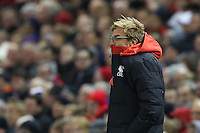 Liverpool Manager Jurgen Klopp huddles in his coat as the winds from Storm Clodagh swirl around Anfield during the Barclays Premier League Match between Liverpool and Swansea City played at Anfield, Liverpool on 29th November 2015