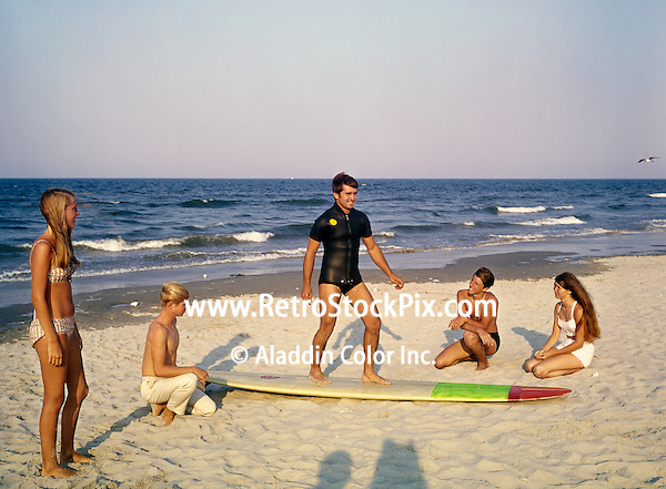 Young men standing on surf board teaching kids how to surf.