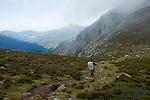 A woman hiking along a path, descending into a valley in Corsica, France.