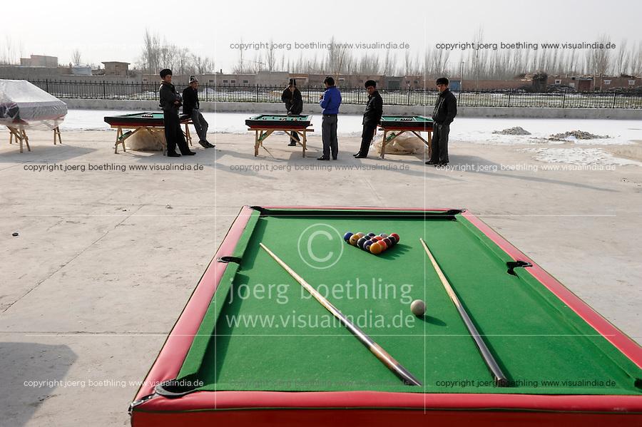 CHINA province Xinjiang city Kashgar where uyghur people are living , uighur men play pool outdoor in winter time / CHINA Provinz Xinjiang , Stadt Kashgar hier lebt das muslimische Turkvolk der Uiguren die durch massive Zuwanderung von Han Chinesen zur Minderheit werden , Uiguren spielen draussen Billiard im Winter