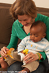9 month old baby boy with mother language development show toy animals as she talks to him (child adopted from Ethiopia as an infant)