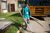 """Adam Madamba moves wood to a dumpster during """"Circle the City with Service,"""" the Kiwanis Circle K International's 2015 Large Scale Service Project, on Wednesday, June 24, 2015, at the Friendship Westside Center for Excellence in Indianapolis. (Photo by James Brosher)"""