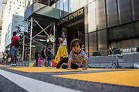 """NEW YORK, NY - JULY 9: A boy sits on the """"Black Lives Matter"""" mural in front of the Trump Tower in New York, NY on July 9, 2020. Bill de Blasio, Mayor of New York and founders of National Action Network Inc. (NAN) paints a """"Black Lives Matter"""" mural along Fifth Avenue in front of the Trump Tower in New York. President Donald Trump criticized the mayor's plan to paint a street mural in front of Trump Tower. (Photo by Pablo Monsalve / VIEWpress via Getty Images)"""