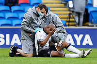Andre Ayew of Swansea City (C) is seen to by Ritson Lloyd (L) and Jez McCluskey, Club Doctor (R) during the Sky Bet Championship match between Cardiff City and Swansea City at the Cardiff City Stadium, Cardiff, Wales, UK. Saturday 12 December 2020