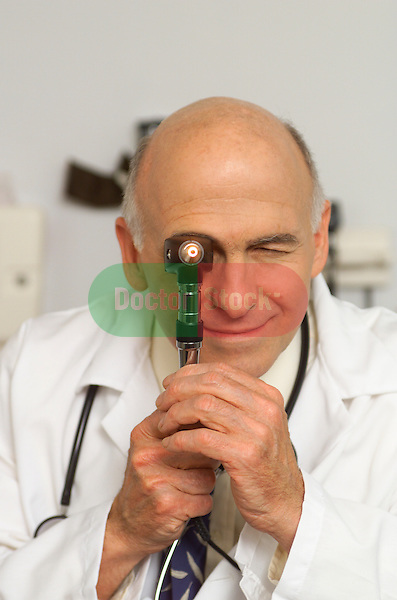 older, elder male doctor looking directly at camera through otoscope