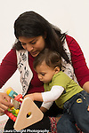 Baby boy 12 months old sitting with mother shown how sliding bead and shape toy works joint attention