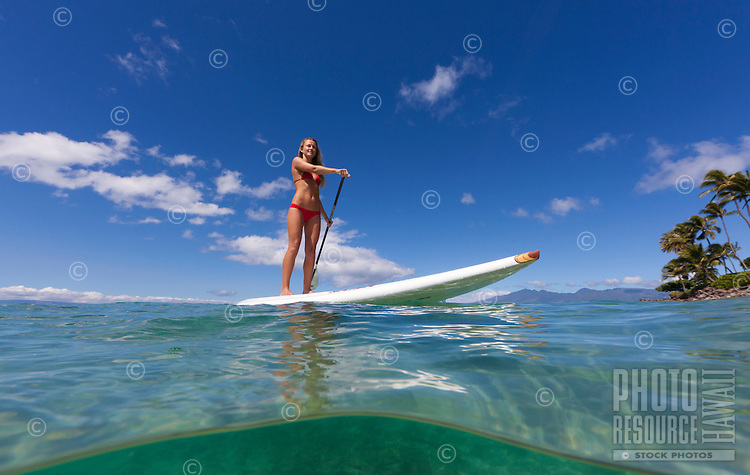 A woman enjoys a beautiful day standup paddling at Napili Bay, Maui.