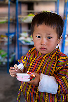 Punakha, Bhutan.  Young Boy in Traditional Male Gho Garment, Eating Ice Cream in the Lobeysa Market.