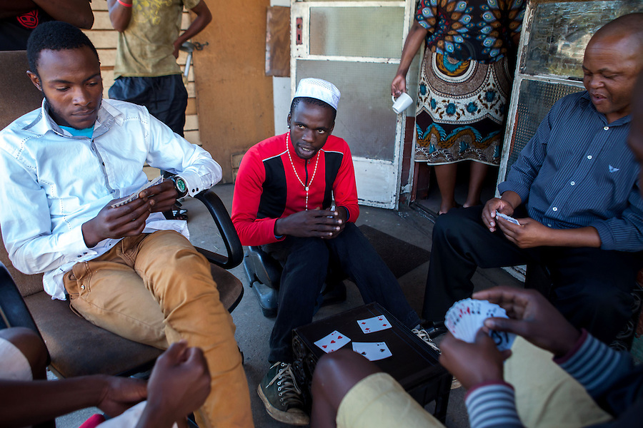 """A group of men play casino at """"Skomplaas"""" hostel, one of Durban Deep Goldmine's old hostels on the outskirts of Johannesburg, South Africa."""