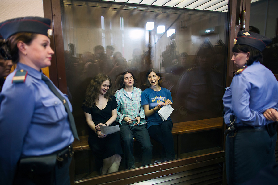 17/08/2012, Moscow, Russia..Maria Alyokhina, Yekaterina Samutsevich and Nadezhda Tolokonnikova of punk band Pussy Riot laughing inside the courtroom's glass cage after being sentenced to two years in prison for their performance in the Christ The Saviour Cathedral.