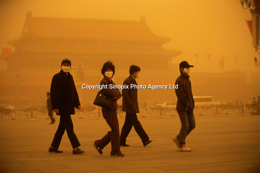 Tourists wear respirator while walking in the Tananmen Square in Beijing, China. A dust storm strikes Beijing, turning the sky an amber color and reducing visibility to about 1/3 mile. Extensive deforestation and desertification in northern China have fueled the dust storms. Nearly one million tons of Gobi Desert sand blows into Beijing each year..20-MAR-02