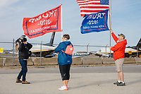 A videographer for Australia's Channel 9 news photographs two Trump supporters carrying flags outside the Make America Great Again Victory Rally in the final week before the Nov. 3 election at Pro Star Aviation in Londonderry, New Hampshire, on Sun., Oct. 25, 2020.