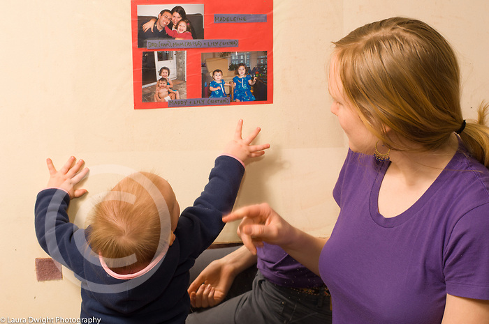 Day Care Center female caregiver with toddler talking to her as she points out family photos on wall