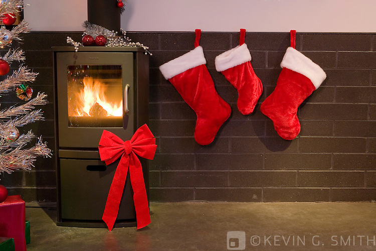 Living room in a modern style home decorated for christmas, 60's retro aluminum Christmas tree, wood stove, stockings hung on block wall.