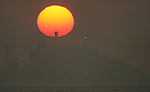 The rising sun sihouetted one of the tops of a towers the Bay Bridge and Alcatraz Island as it slowly appeared out the low lying fog and haze off the San Francisco Bay, California.