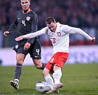 Jacek Krzynowek of Poland strikes the ball as Michael Bradley of the USA looks on. The United States defeated Poland 3-0 during an international friendly at Wisla Stadium in Krakow, Poland on March 26, 2008.