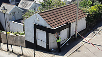 Pictured: A police officer assesses the damage caused to a small building by the David Hathaway articulated lorry which became stuck on Constitution Hill, Wales, UK. Monday 15 July 2019<br /> Re: An articulated lorry that got stuck in Swansea's steepest road, had to be towed away.<br /> The David Hathaway vehicle was attempting to turn from Brooklands Terrace to Constitution Hill just after 11am but successive attempts by the driver proved difficult as the wheels kept losing traction.<br /> Police, a fire service vehicle and a recovery truck attended which helped free the lorry.