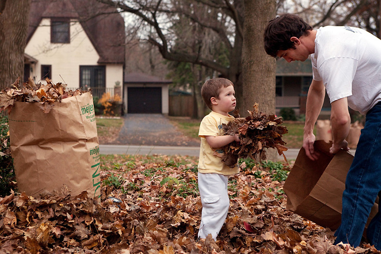 My older son, then three and a half, helps his dad bag leaves in our front yard.