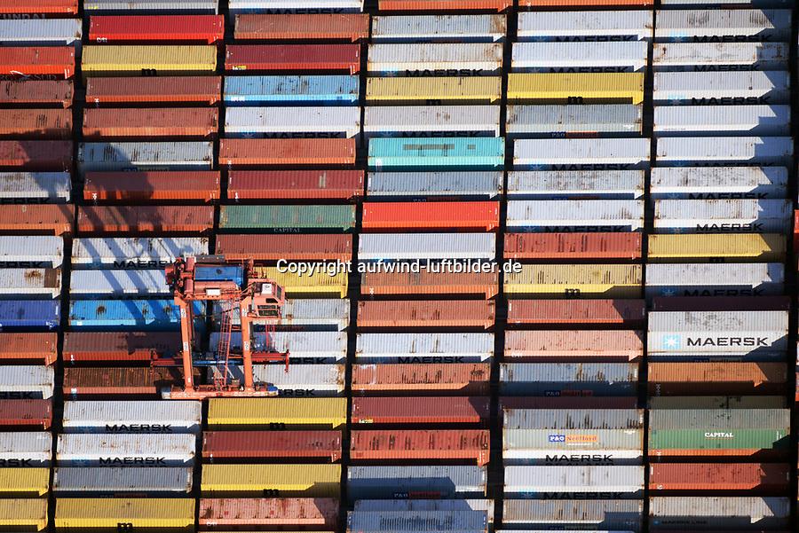 Portalhubwagen transportiert Container am Burchardkai: EUROPA, DEUTSCHLAND, HAMBURG, (EUROPE, GERMANY), 06.02.2018 Der Portalhubwagen (oder Portalhubstapelwagen oder Portalstapelwagen; engl. van carrier, straddle carrier, gantry lift ist ein spezielles Umschlaggeraet fuer ISO-Container. Es wird als Transportfahrzeug auf Containerterminals in Haefen eingesetzt.<br />  <br /> Der Portalhubwagen besteht aus einem Rahmengestell und einer dazwischen haengenden Hubvorrichtung Topspreader, das mit Hubwinden vertikal bewegt werden kann. Das Rahmengestell ist mit einem Fahrwerk mit meist acht Raedern ausgestattet. Die Fahrerkabine ist oben an einer Stirnseite des Rahmens angeflanscht.<br />  <br /> Der Portalhubwagen faehrt ueber einen Container, der auf dem Boden oder auf einem Lkw steht, der Spreader verriegelt sich hydraulisch gesteuert mit den vier Eckbeschlaegen des Containers und hebt diesen an.