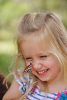 Gulf Fritillary (Agraulis vanillae), girl holding butterfly, Hill Country, Central Texas, USA