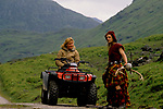 'CLAN, THE' SCOTLAND, A GROUP WHO SPEND THEIR WEEKENDS AT A CAMP IN GLEN CROE, RECREATING THE LIFE OF A SCOTTISH CLAN BEFORE THE DEFEAT OF BONNIE PRINCE CHARLIE BY THE ENGLISH AT THE BATTLE OF CULLODEN IN 1746. DIANE DAVIDSON RIDING QUAD BIKE, STOPS TO TALK WITH THE CLAN CHIEF SEORAS (HIS CLAN NAME) HIS WEEKDAY NAME IS GEORGE, 1989