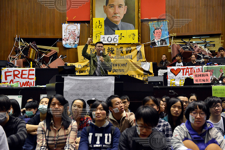 """Student leader Lin Fei-Fan (centre) addresses the amassed students and some of the local press inside Taiwan's Legislative Yuan (Parliament) Building on the 4th day of its occupation by students in opposition to the passing of the Cross-Straight Service and Trade Agreement between Taiwan and China.  The students, and many normal Taiwanese, fear the erosion of their hard-won democracy and, eventually, independence, making them, in the words of one student protestor 'no better off than Hong Kong'. Ma ying-jeoh bears the brunt of the protestors ire; known as """"Ma 9%"""" after his latest approval rating, he is seen as kowtowing to the demands of China and selling out Taiwan."""