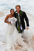 A couple in wedding attire walking out of the ocean at Waimea Bay Beach Park
