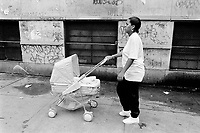 """USA. New York City. Spanish Harlem. Lady is 15 years old and is the single mother of Shana. She walks in the street with her child's stroller. Lady and her Puerto Rican family live below the poverty line and receives public assistance (AFDC, Home Relief, Supplemental Security Income and Medicaid). The family resides in units managed by the New York City Housing Authority (NYCHA) which provides housing for low income residents. NYCHA administers rental apartments in facilities, popularly known as """"projects"""". Spanish Harlem, also known as El Barrio and East Harlem, is a low income neighborhood in Harlem area. Spanish Harlem is one of the largest predominantly Latino communities in New York City. 06.09.89 © 1989 Didier Ruef .."""