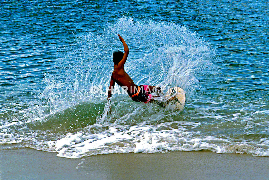 Garoto praticando sorrisal ou surf em disco.  Ubatuba. São Paulo. 1991. Foto de Juca Martins.