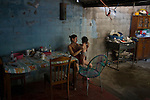 """November 08, 2014. """"Water it´s the real thing""""<br /> Siomara Raquel Castro with her child Bradley Jared in her home in Nejapa (El Salvador). She doesn' t have water at home. The people of Nejapa have no drinking water because the Coca -Cola company overexploited the aquifer in the area, the most important source of water in this Central American country. This means that the population has to walk for hours to get water from wells and rivers. The problem is that these rivers and wells are contaminated by discharges that makes Coca- Cola and other factories that are installed in the area. The problem can increase: Coca Cola company has expansion plans, something that communities and NGOs want to stop. To make a liter of Coca Cola are needed 2,4 liters of water. ©Calamar2/ Pedro ARMESTRE"""