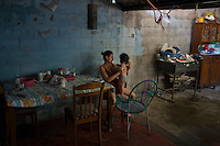 "November 08, 2014. ""Water it´s the real thing""<br /> Siomara Raquel Castro with her child Bradley Jared in her home in Nejapa (El Salvador). She doesn' t have water at home. The people of Nejapa have no drinking water because the Coca -Cola company overexploited the aquifer in the area, the most important source of water in this Central American country. This means that the population has to walk for hours to get water from wells and rivers. The problem is that these rivers and wells are contaminated by discharges that makes Coca- Cola and other factories that are installed in the area. The problem can increase: Coca Cola company has expansion plans, something that communities and NGOs want to stop. To make a liter of Coca Cola are needed 2,4 liters of water. ©Calamar2/ Pedro ARMESTRE"