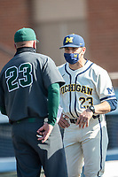 Michigan Wolverines head coach Erik Bakich (23) meets with Michigan State Spartans head coach Jake Boss Jr. (23) on March 21, 2021 before the NCAA baseball action at Ray Fisher Stadium in Ann Arbor, Michigan. Michigan scored 8 runs in the bottom of the ninth inning to defeat the Spartans 8-7. (Andrew Woolley/Four Seam Images)