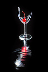 Broken wine glass on black background with cherry and reflections.  Photographed in-studio on reflective mat.