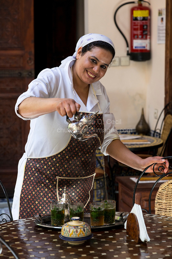 Fes, Morocco.  Woman Pouring Tea for Guests.