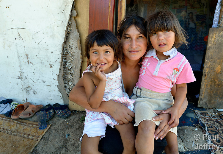 Mirjava Memetovic holds her daughters Kristina (left) and Laura, in front of their makeshift home in Palilula, a neighborhood of Belgrade, Serbia. They are Roma, also known as Gypsies, and were expelled in 2012 from the center of Belgrade to make way for new apartments and office buildings. Because Memetovic had no identity documents, she was sent with her daughters to her native village in the south of the country, but soon returned as she had no way to survive there. She and her daughters beg for money at a fast food restaurant near their squatter settlement.