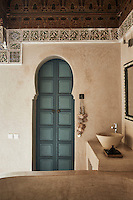 Decorative tiles run around the top of the wall in the bathroom and a washbasin is set on a marble unit in one corner of the room.