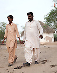 25 JULY 2011: Basti Mahraan Village, Punjab, Pakistan.    Mahar Abdul Latif (R), a former member of Muslim terrorist group Lashkar-i-Taiba (LeT) at his home village of Basti Mahraan in Pakistan with fellow villager Bachu Ram, a Hindu. After Ram offered to donate his rare blood type to save the life of a muslim woman, relations thawed in the traditional violence between the Muslims and Hindu's of the village. The men are walking from a Hindu temple that was renovated by the Muslim's of the village in a sign of solidarity.Picture by Graham Crouch/Toronto Star