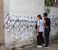 Suzhou, Jiangsu, China.  Couple Examining Tags Containing Hopes for Good Wishes, left by Passersby.  Shantang District.