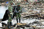Indonesian soldiers prepare to wrap up a body in downtown Banda Aceh, Indonesia on January 15, 2005.  The Asian tsunami killed over 110,000 in Indonesia.  (photo by Khampha Bouaphanh)