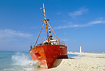 Portugal, Algarve, Insel Ilha Da Culatra: gestrandets Schiff am Strand, im Hintergrund der Leuchtturm der Insel | Portugal, Algarve, Island Ilha Da Culatra: Ship Wreck at beach