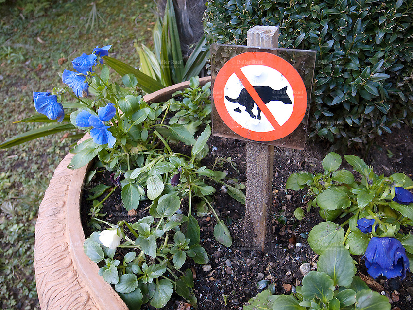 Switzerland. Canton Ticino. Lugano. A sign in a garden bush prohibits any dogs to defecate. No dogs allowed. 22.01.11 © 2011 Didier Ruef
