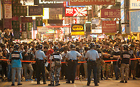 Pro-democracy protesters are seen behind a police cordon, shortly before the Hong Kong police lost control of the area, and thus ceding it back to the protesters, who had only just lost it to the police hours earlier in a pre-dawn raid, Mong Kok, Kowloon, Hong Kong, China, 18 October 2014.